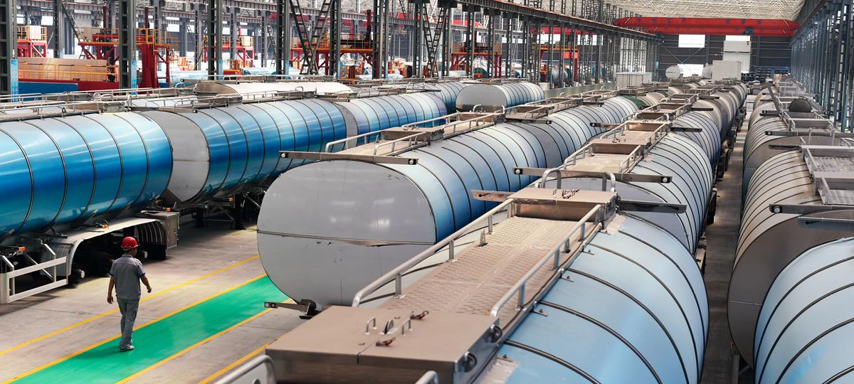 邹平市轻质高强铝合金生产基地的明航智能物流装备公司工人从要出售的铝合金罐车旁走过,该公司生产20余种高强铝合金罐车。